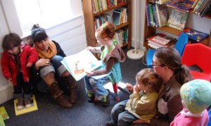 Kindergartener Emma Sulger, a former story hour regular, reads to thelittle guysat a recent story hour, every Wednesday at 11 AM.